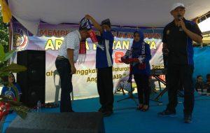 Ketua paguyuban Arema Bintan Raya Pramuji menyerahkan tumpeng kepada Andi Chori